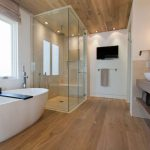 Amazing-Contemporary-Bathroom-design-ideas-with-white-curved-bathtub-and-glass-shower-area-and-laminated-wood-flooring-ideas-915x609