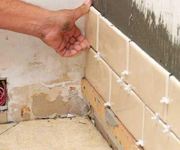 Кирпичная кладка прямоугольной плитки на стене в ванной комнате
