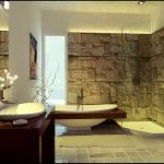 fascinating-modern-bathroom-design-ideas-with-natural-stone-on-walls-also-oval-white-porcelain-standing-bathtub-and-oval-white-sink-on-shiny-black-table-and-rectangle-grey-carpet-on-gradation-grey-til