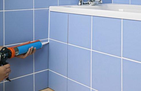 Рабочий процесс – укладывает плитку в ванной своими руками